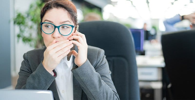 Young woman at the office who saw a folder containing top secret information because access-based enumeration was not activated; now she is on the phone with someone.