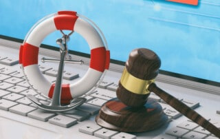 Judge's gavel and life preserver on a computer keyboard representing safe haven for data breaches.