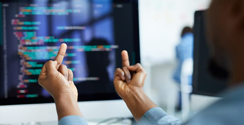 Cover image for an article about file server migration. IT admin showing both middle fingers to code on screen.