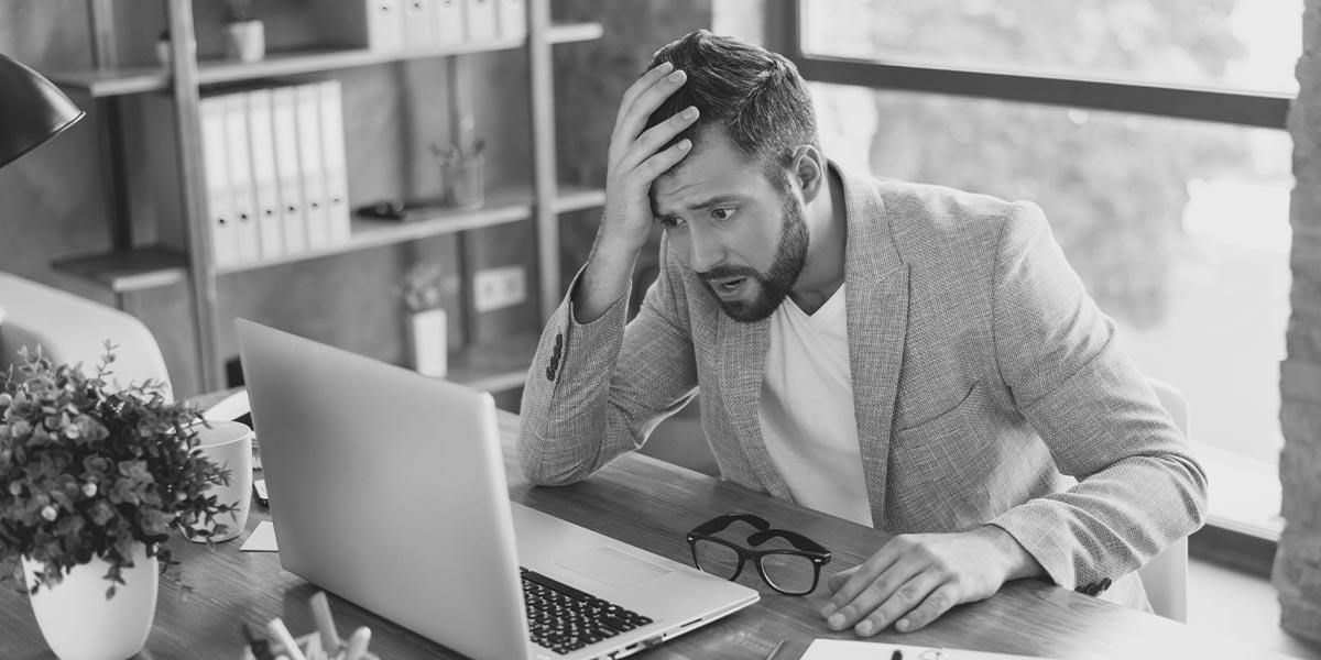 Business Mann, der ungläubig auf seinen Bildschirm starrt. IAM Software Vergleich.