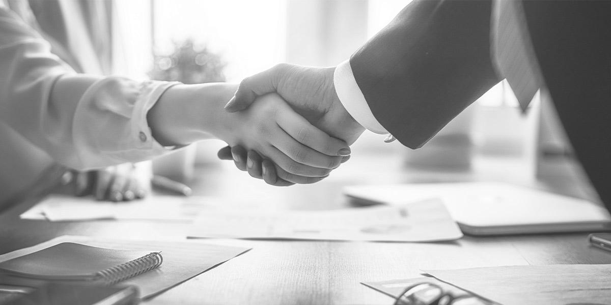 Business Meeting, bei dem sich zwei Geschäftsleute die Hände reichen.