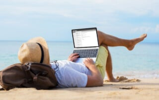 Employee sitting on the beach forgot to set his out of office message and has to use his company laptop to fix it.