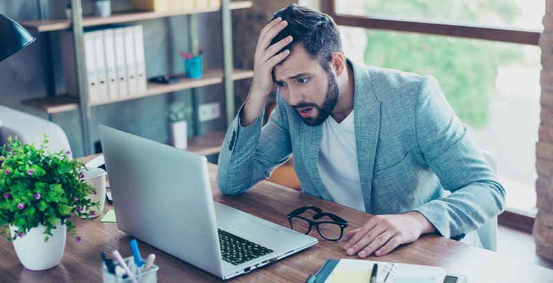 Business man staring at his screen in disbelief. IAM Software compared.