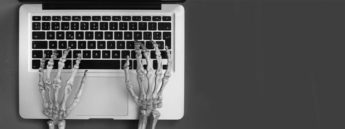 Skeletthände auf einer Tastatur.