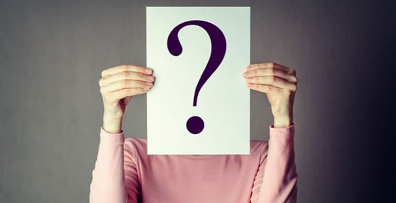 Young woman holding a piece of paper with a question mark in front of her face. Identity management vs. access management.